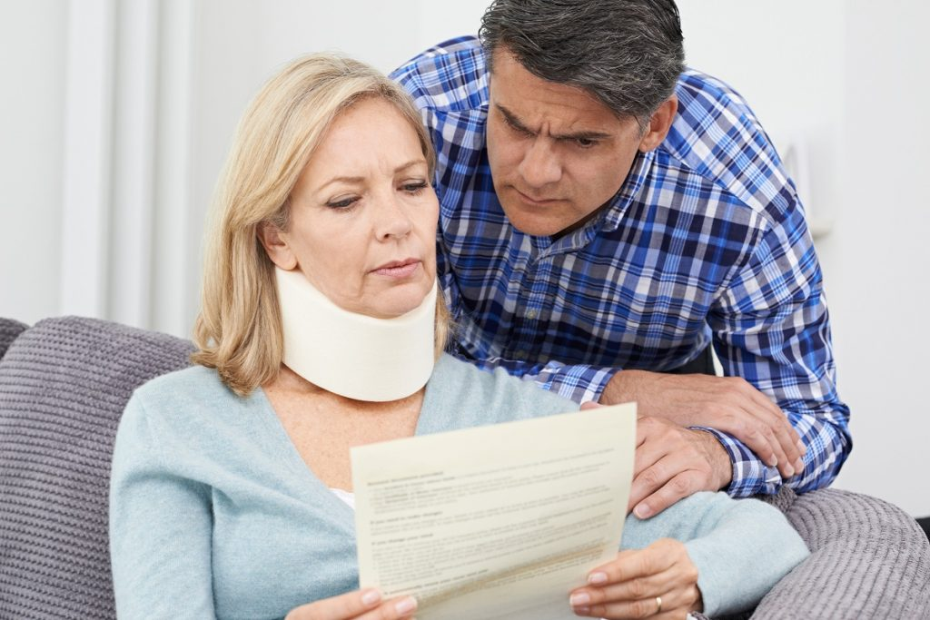 Couple reading insurance policy after a car accident