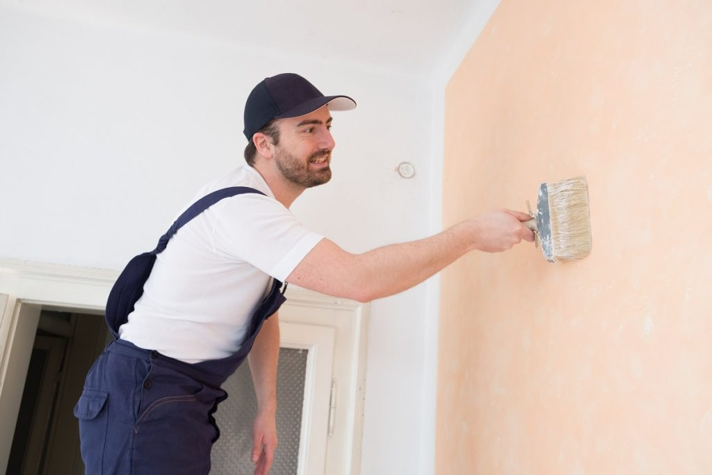 Man painting the house with peach