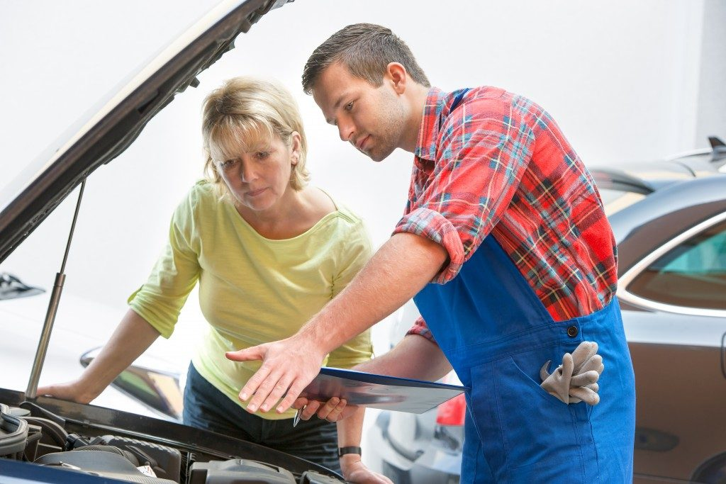 Mechanic showing the lady the parts of the car