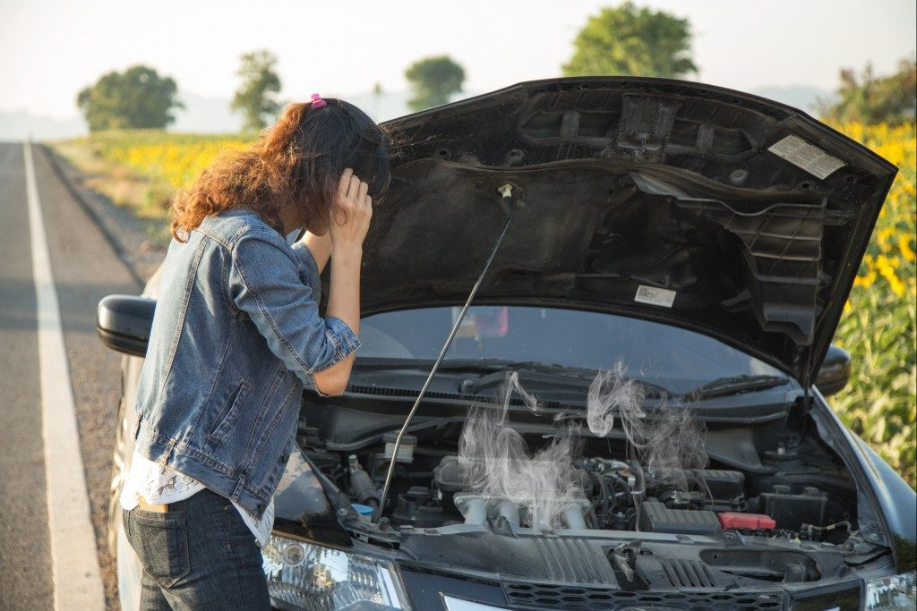 woman checking her broke down car
