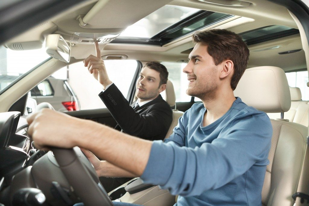 Salesman showing car feature to client