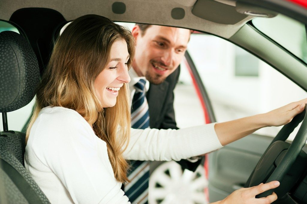 Woman checking a new feature on a car