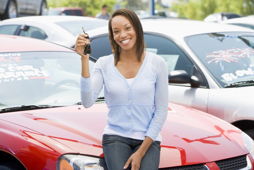Woman picking up bought car from lot