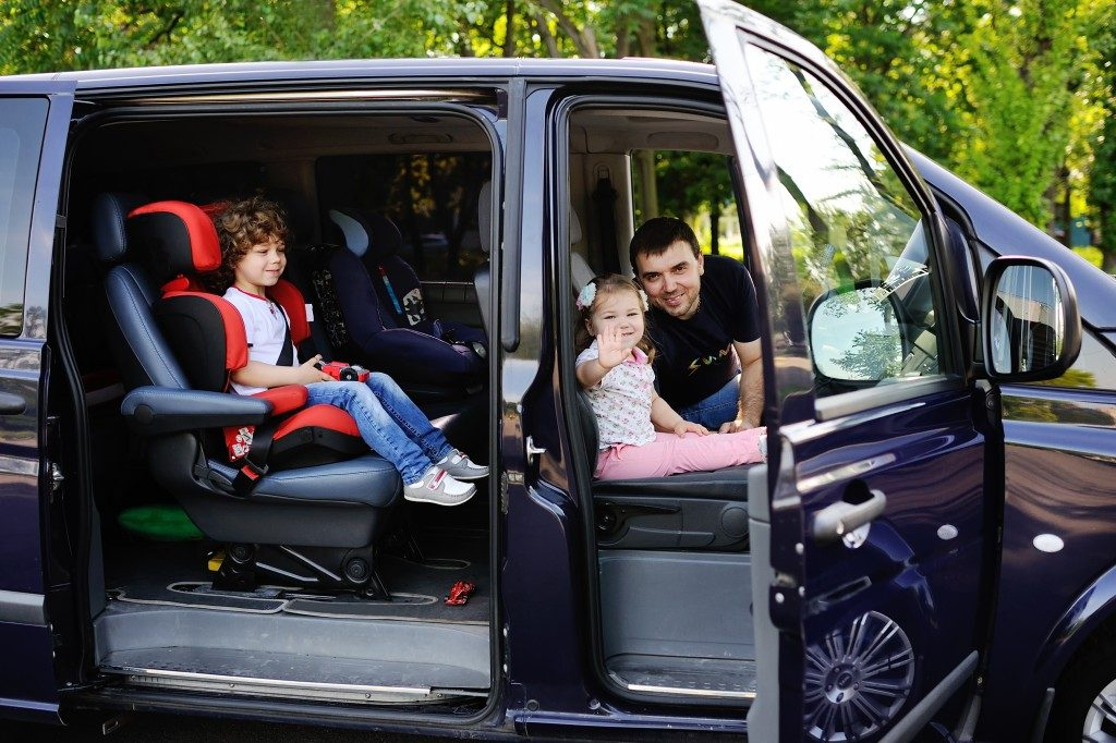 Father with son and daughter sitting in the salon van and smiling