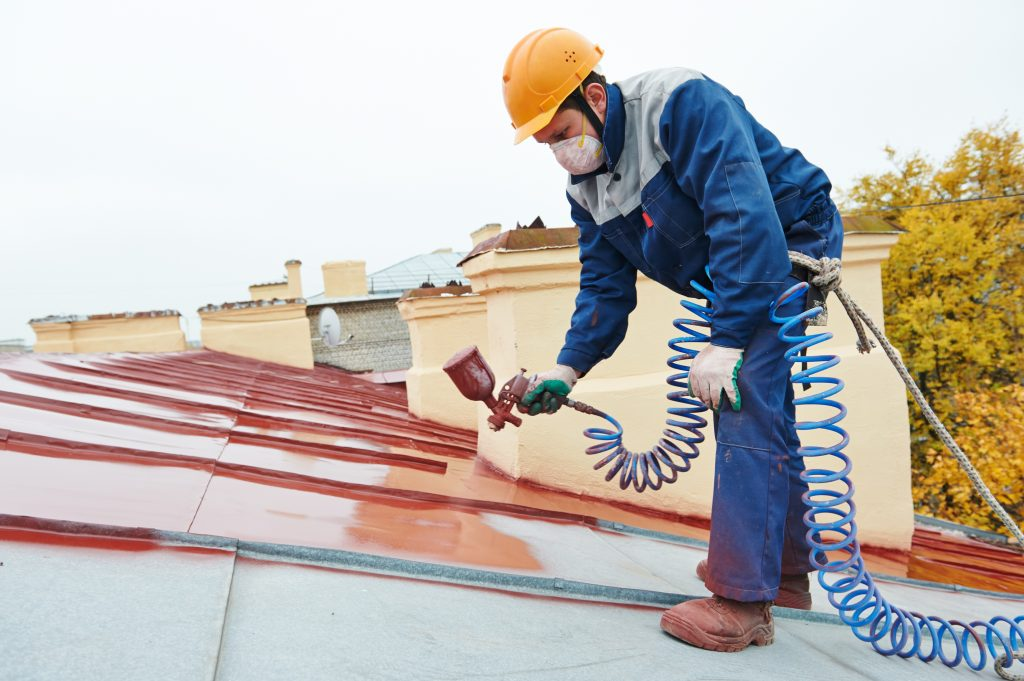 man painting the roof
