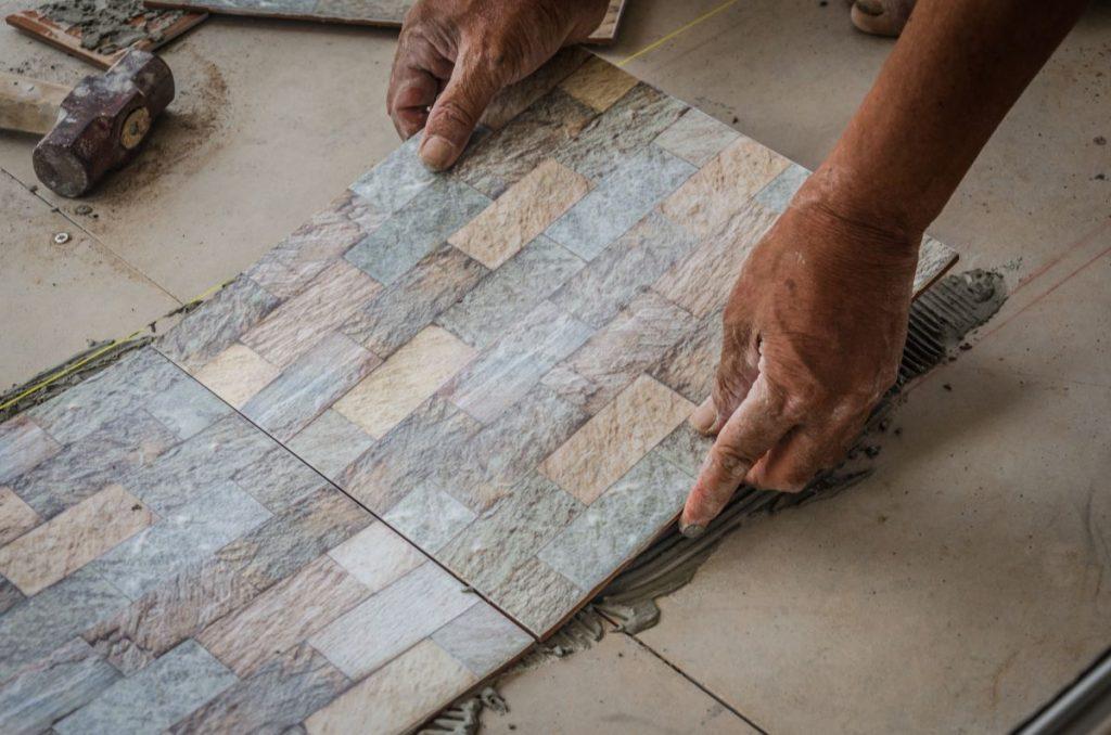 man setting down flooring tiles