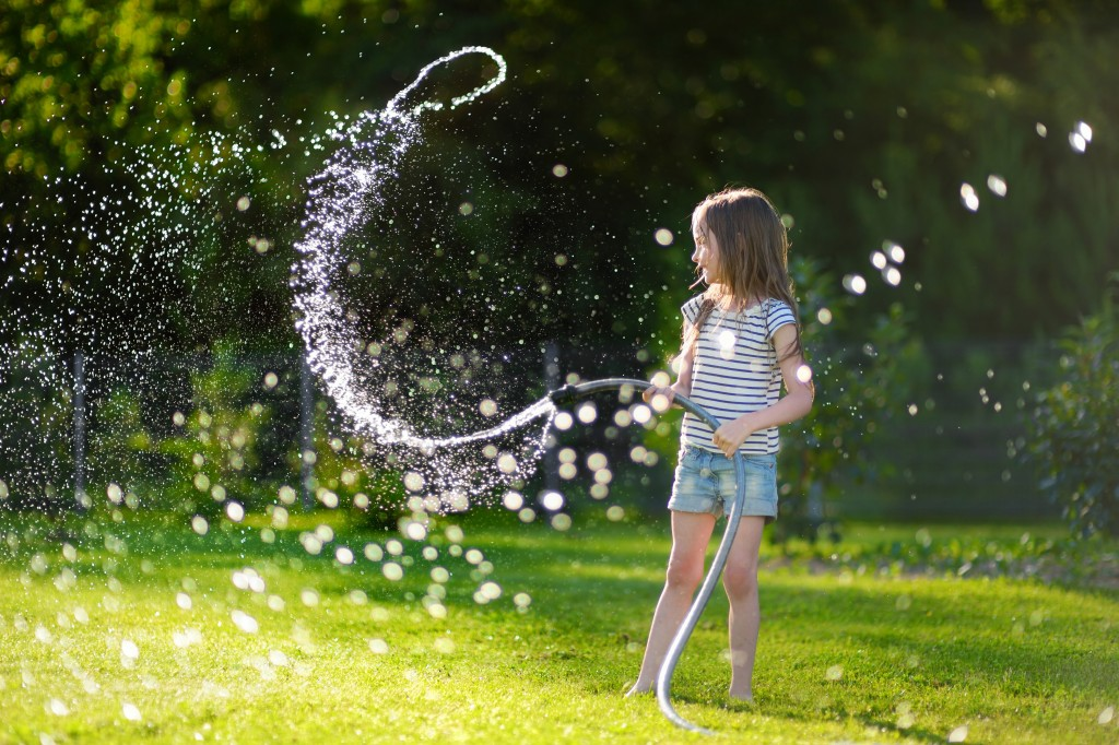 kid playing with garden hose