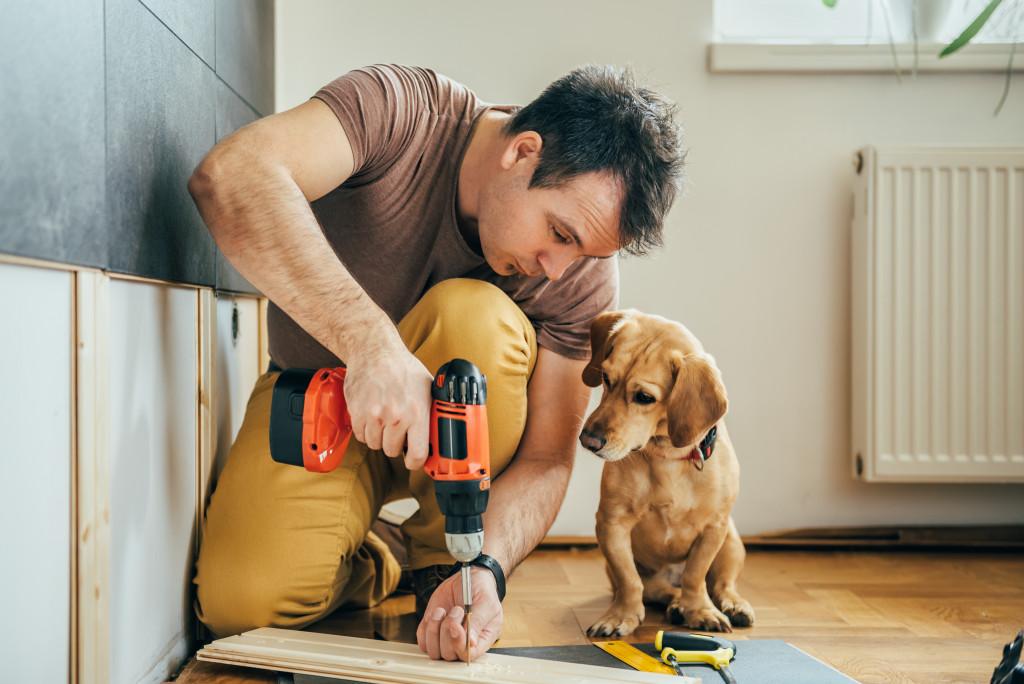 man doing DIY work with dog